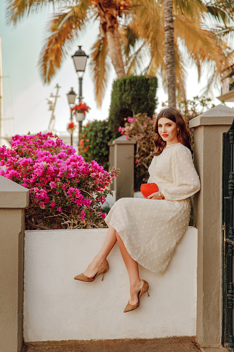 larisa costea, larisa style, larisa costea blog, puerto de mogan, travel blog, fashion blog, gran canaria, traveler, wanderlust, bougainvilles, palm trees, ootd, outfit inspiration, valentine's day, vday look, vday outfit, chicwish, white midi dress, buttery dress, pom pom dress, santi heart shaped clutch, shopbop, kurt geiger beige shoes, heels, flowers, port town, best destination, best location, red lipstick, feminine look, lady like